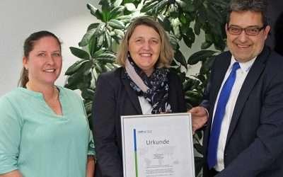 Drei Personen in einem Raum vor Pflanzen mit einer klimaneutral Post Urkunde